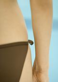 Woman wearing string bikini, close-up of hip, rear view
