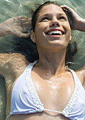 Woman lying in shallow water, smiling