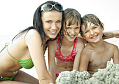 Young woman and two children on beach, smiling at camera