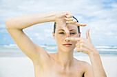 Woman on beach making finger frame around eye, head and shoulders