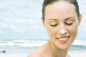 Woman on beach with sunscreen on nose, head and shoulders