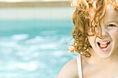 Little girl laughing at camera, portrait, swimming pool in background