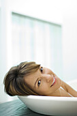 Woman leaning head against side of bathtub, smiling at camera, close-up