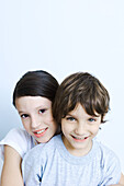 Sister hugging her brother from behind, smiling at camera, portrait