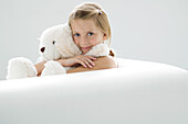 Girl holding teddy bear, smiling at camera