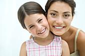Mother and daughter cheek to cheek, both smiling at camera