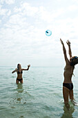 Teen friends waist deep in water playing with beach ball