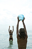 Teen girls playing with beach ball in sea
