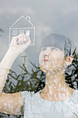 Young woman drawing house on windowpane, daydreaming