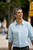 Man walking outdoors, smiling, looking away