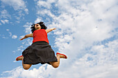 Young woman jumping in midair, low angle view