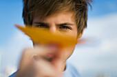 Young man aiming paper airplane at camera