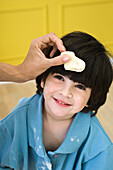 Parent holding dough against little boy's head, cropped