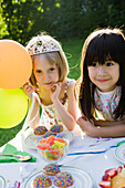 Girls admiring sweets table at outdoor party