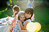 Young friends embracing at outdoor party, portrait