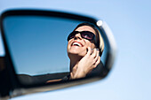 Woman talking on cell phone, reflection in side-view mirror