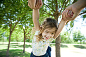 Little girl being swung through air by her arms