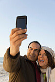 Mature couple photographing themselves with photophone