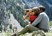 Spain, Catalonia, father and daughter looking at view, girl using binoculars
