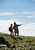 Hikers, man pointing with walking stick