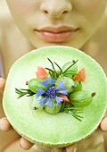 Woman holding up honeydew melon topped with berries, flower and rosemary sprigs, close-up