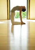 Yoga class, woman doing camel pose