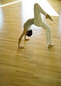 Yoga class, woman doing one-legged bridge pose
