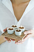 Woman holding tray of candles, close-up, cropped