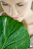 Young woman holding leaf up to face, close-up, cropped