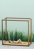 Woman wearing bikini, lying on back in square structure near lake