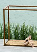 Woman wearing bikini, sitting in wooden structure, near lake