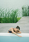 Woman leaning against edge of pool, touching surface of water, lake in background