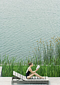 Woman sitting up on lounge chair, reading, next to lake