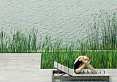 Woman sitting on lounge chair next to lake, hugging knees, resting head on arms