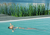 Woman floating on back in pool, full length, lake in background