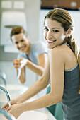 Two women washing hands in public restrooms