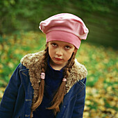 Girl outside wearing pink beret, winter coat, pouting, looking at camera