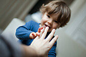 Toddler boy touching parent's hand