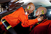 Two crash test dummies about to kiss inside a car