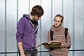 A teenage boy and girl looking at a school workbook together