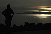A silhouetted woman looking at a view of the Adriatic Sea near Unije, Croatia