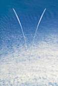 Two airplanes and vapor trails in the sky