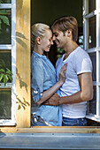 A cheerful couple embracing in front of an open window