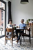 A cheerful hip mixed age couple enjoying breakfast together in their dining room