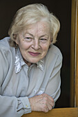 A senior woman leaning on a window sill, smiling while looking away
