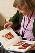 A senior woman looking through a photo album