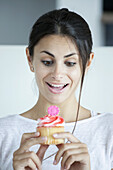 Woman pleased with flower-head cupcake