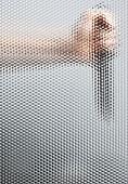 A human hand holding a knife behind a beveled glass window