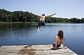 Guy dives into lake with arms outstretched as girl watches on jetty