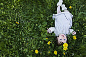 A cheerful baby girl lying in the grass, looking up